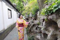 Den traditionella asiatiska japanska härliga kvinnan bär kimonot i en vårträdgård parkerar ställningen vid bambu tycker om fri ti Royaltyfria Foton