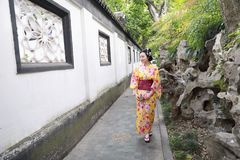 Den traditionella asiatiska japanska härliga kvinnan bär kimonot i en vårträdgård parkerar ställningen vid bambu tycker om fanen  Arkivbild