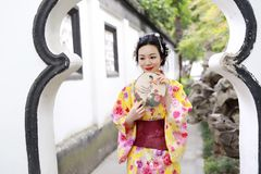 Den traditionella asiatiska japanska härliga kvinnan bär kimonot i en vårträdgård parkerar ställningen vid bambu tycker om fanen  Royaltyfria Foton