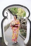 Den traditionella asiatiska japanska härliga kvinnan bär kimonot i en vårträdgård parkerar ställningen vid bambu tycker om fanen  Fotografering för Bildbyråer