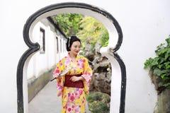 Den traditionella asiatiska japanska härliga kvinnan bär kimonot i en vårträdgård parkerar ställningen vid bambu tycker om fanen  Royaltyfri Fotografi