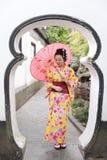 Den traditionella asiatiska japanska härliga kvinnan bär kimonot i en vårträdgård parkerar ställningen vid bambu tycker om fanpar Royaltyfri Bild