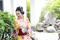 Den traditionella asiatiska japanska härliga kvinnan bär kimonot med fanen förestående som ler att spela på utomhus- vårträdgård Arkivbild