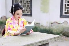 Den traditionella asiatiska japanska härliga kvinnan bär kimonot med fanläseboken i utomhus- vårträdgård Royaltyfri Fotografi