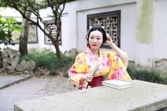 Den traditionella asiatiska japanska härliga kvinnan bär kimonot med läseboken för fanen förestående i utomhus- vårträdgård Arkivbilder