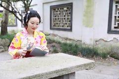 Den traditionella asiatiska japanska härliga kvinnan bär kimonot med läseboken för fanen förestående i utomhus- vårträdgård Royaltyfri Bild