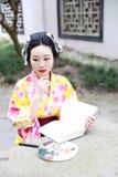 Den traditionella asiatiska japanska härliga kvinnan bär kimonot med läseboken för fanen förestående i utomhus- vårträdgård Royaltyfri Foto