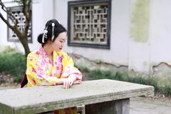 Den traditionella asiatiska japanska härliga kvinnan bär kimonot sitter på stenbänk i utomhus- vårträdgård Arkivfoton