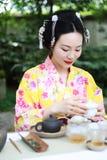 Den traditionella asiatiska japanska härliga kvinnan bär konst för kimonoshowte, och ceremoni sitter på stenbänk i utomhus- vårtr Fotografering för Bildbyråer