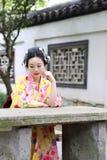 Den traditionella asiatiska japanska kvinnan i en utomhus- trädgård sitter på en stenbänk Arkivbild