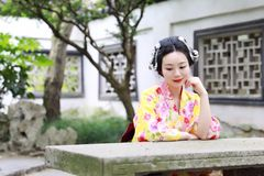 Den traditionella asiatiska japanska kvinnan i en utomhus- trädgård sitter på en stenbänk Arkivbilder