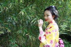 Den traditionella asiatiska japanska kvinnan med den japanska bruden för kimonot som ler ställningen vid bambu i en vår, parkerar Royaltyfri Foto