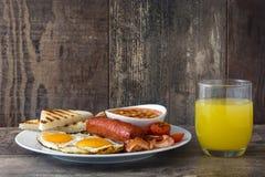 Den traditionella fulla engelska frukosten med stekte ägg, korvar, bönor, champinjoner, grillade tomater och bacon Arkivbild