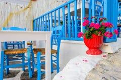 Den traditionella grekiska restaurangen på den öppna luften med ljusa blått presiderar och blommar Royaltyfri Fotografi