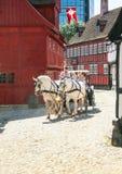 Den traditionella hästtriumfvagnen och trähus på hålan spelar förbi i Århus royaltyfria bilder
