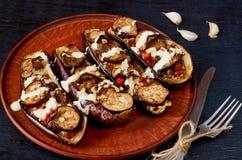 Den traditionella italienska maträtten - grillade aubergine som stoppades med löneförhöjning, tomater, vitlök och sås på en tappn royaltyfria foton