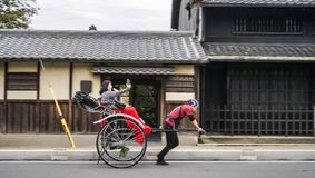Den traditionella japanska vagnshanden drog rickshawen i Nara med gladlynta turister som tar fotoselfi på telefonen arkivfoto