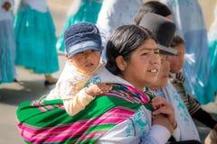 Den traditionella kvinnan Cholita i typisk kläder med behandla som ett barn på henne tillbaka under 1st Maj som den arbets- dagen Royaltyfria Foton
