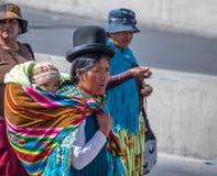 Den traditionella kvinnan Cholita i typisk kläder med behandla som ett barn på henne tillbaka under 1st Maj som den arbets- dagen Fotografering för Bildbyråer