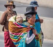 Den traditionella kvinnan Cholita i typisk kläder med behandla som ett barn på henne tillbaka under 1st Maj som den arbets- dagen Royaltyfri Foto