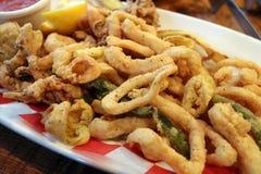 Den traditionella läckra stekte calamarien ringer med stekte grönsaker Arkivfoton