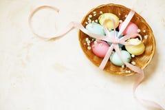 Den traditionella mallen för det easter kortet med pastellfärgade färger målade organiska ägg i vide- korg med hö och dekorativa  Royaltyfri Bild