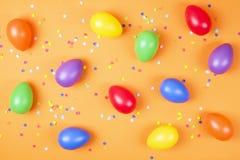 Den traditionella mallen för det easter kortet med pastellfärgade färger målade organiska ägg i vide- korg med hö och dekorativa  Royaltyfri Foto