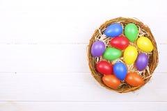 Den traditionella mallen för det easter kortet med pastellfärgade färger målade organiska ägg i vide- korg med hö och dekorativa  Arkivbild