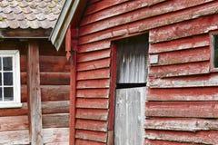 Den traditionella norska träröda kulöra kabinen inhyser fasader Nolla Royaltyfri Bild