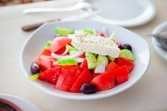 Den traditionella nya grekiska sallad, frappe och brusketaen tjänade som för lunch på det utomhus- kafét Arkivbild