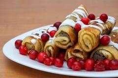 Den traditionella sötsaken rullade pannkakor med vallmofrön på plattan Arkivfoton