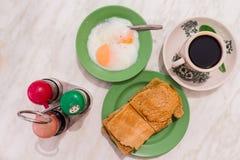 Den traditionella Singapore frukosten kallade Kaya Toast, kaffebröd med kokosnötdriftstopp och Halva-kokade ägg Royaltyfria Bilder