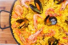 Den traditionella spanjoren besegrar paella med räkor och musslor Arkivbild