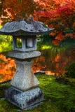 Den traditionella stenlyktan och röda lönnar i en japan arbeta i trädgården under höst royaltyfria bilder