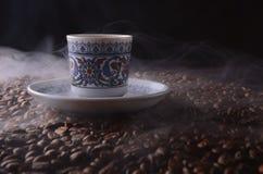 Den traditionella varma kaffekoppen med bönor och rök ångar över en bla Arkivfoton