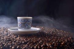 Den traditionella varma kaffekoppen med bönor och rök ångar över en bla Royaltyfri Foto