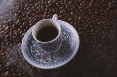 Den traditionella varma kaffekoppen med bönor och rök ångar över en bla Arkivbilder