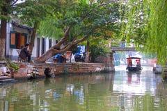 Den traditionella vattentaxien reser under bron, Zhujiajiao, Kina Arkivbild