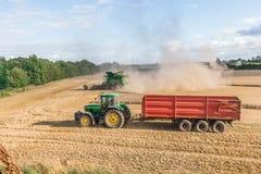 Den traktorvagnen och sammanslutningen bearbetar med maskin förlovat i plockningkorn arkivbild