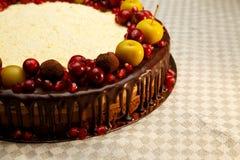 Den trefaldiga chokladkakan dekorerade med granatäpplet, tranbär och små äpplen Arkivfoto