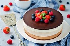 Den trefaldiga kakan för chokladmousse dekorerade med nya bär Royaltyfri Foto