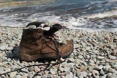 Trekking kängor på en segla utmed kusten arkivbilder