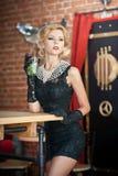 Den trendiga attraktiva damen med den lilla svarta klänningen och långa handskar som står nära en restaurang, bordlägger att ha e Fotografering för Bildbyråer