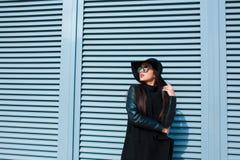 Den trendiga brunettdamen bär exponeringsglas och hatten på gatan W Arkivfoto