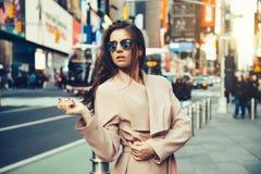 Den trendiga flickan som går på den New York City gatan i bärande solglasögon för Midtown och, knackar omslaget arkivbilder