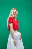 Den trendiga gulliga blonda kvinnan med långt hår och glasögon som bär den vita kjolen och den röda överkanten för kortslutning,  royaltyfri fotografi
