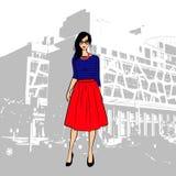 Den trendiga gulliga brunettflickan i en randig överkant och röda midi kringgår i staden Royaltyfri Bild