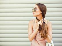 Den trendiga härliga brunettflickan i solglasögon väver flätade trådar på bakgrundsväggen Sommar Arkivbild