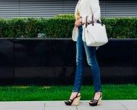 Den trendiga härliga stora vita handväskan på armen av flickan i trendig jeans och innegrejen färgade blusen Arkivfoto