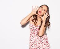 Den trendiga härliga flickan som skriker med hennes händer, vek hornet på en vit ljus bakgrund Hon bar en kort sommarklänning Sex Arkivfoto